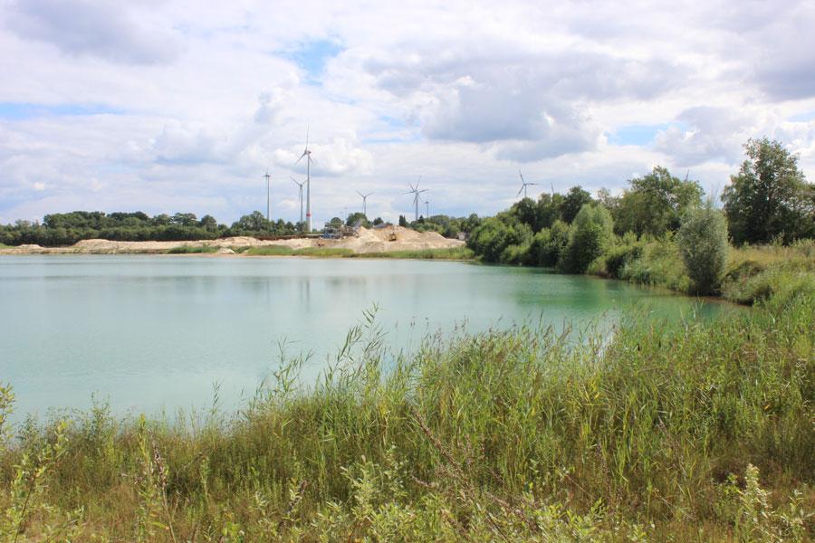 Foto zeigt eine Landschaftsaufnahme eines Sees mit Windkraftanlage im Hintergrund