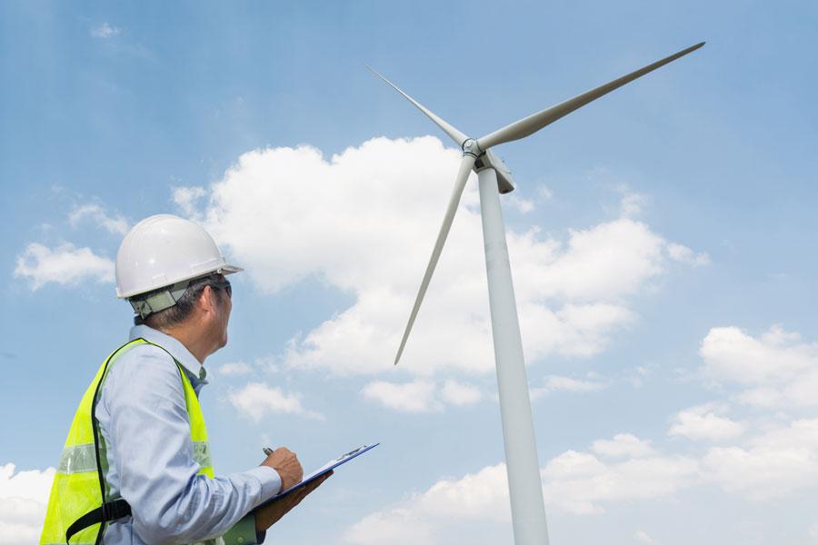 Foto zeigt einen H&M Ingenieurbüro Gutachter vor einer Windkraftanlage | Baubegleitung