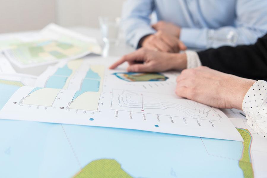 Foto zeigt H&M Mitarbeiter bei der Projektplanung anhand von Kartenmaterial   Gutachten und Planung
